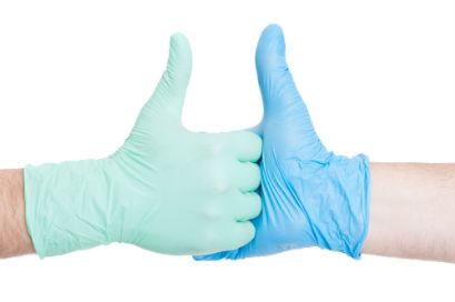 ידיים עם כפפות רפואיות, לוחצות אחת את השנייה ומרימות אגודלים למעלה