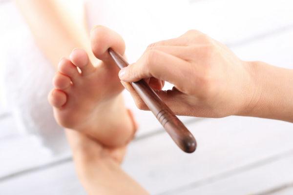 מטפל אקופרסורה לוחץ על אגדול רגל ימין של מטופל
