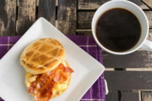 טוסט בייקון ובחיתה לצד כוס קפה על שולחן עץ