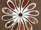 מבחר צמחי מרפא סיניים בצלוחיות על שולחן עץ אלון