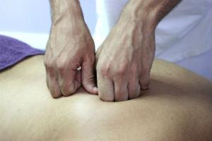 ידיים של מעסה על גבי גבו של מטופל