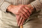 ידיים של גבר קשיש אוחזות במקל הליכה