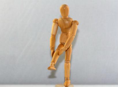 דמות עץ אוחזת בברך